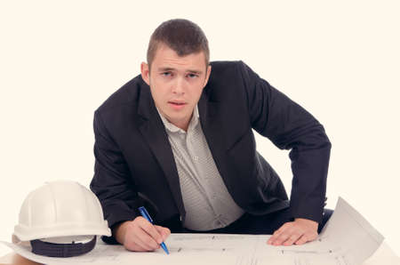 earnest: Young architect or structural engineer bending over a small table checking a blue print drawing with his hardhat alongside