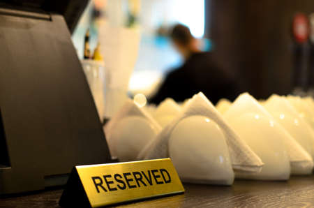 serviettes: reserved sign and crockery with folded paper serviettes on a bar counter ready to be used at table for customers Stock Photo
