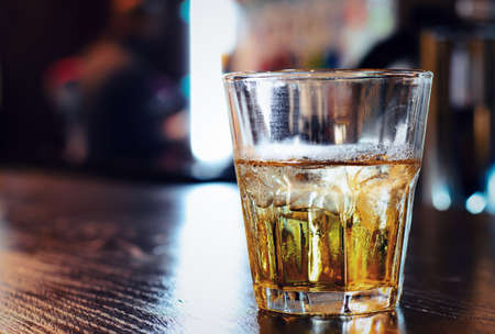 addictive drinking: Close up of a tumbler or glass of whiskey or brandy on a wooden bar counter backlit by light from a window