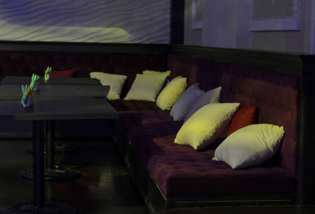 nightspot: Empty tables and comfortable upholstered benches with cushions in a bar or nightclub in dim light Stock Photo