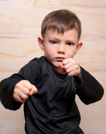 vindictive: Close up Serious White Fighter Male Kid in Black Clothing Posing with Closed Fists While Looking at the Camera.