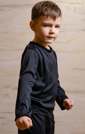 vindictive: Portrait of Strong Serious Male Kid in Black Attire, Posing in Front Wooden Wall While Looking at the Camera.