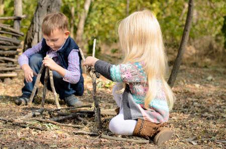 Stijlvolle kleine jongen en meisjes spelen in het bos met stokken gelukkig samen gehurkt op de grond bouwen van verschillende structuren Stockfoto