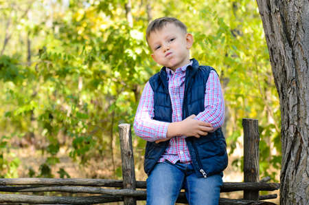 Close up Handsome Little Boy in Autumn Fashion Sitting on Wooden Garden Fence While Looking at the Camera. Captured with Trees at the Back. photo