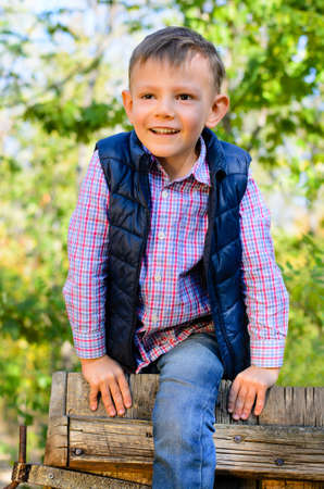 Happy attractive little boy climbing over a wooden fence or gate with a joyful smile outdoors in woodland photo