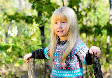 cute girl with long hair: Close up Smiling Little Blond Girl in Autumn Clothing Playing at the Garden. Captured her While Looking Right Frame. Stock Photo