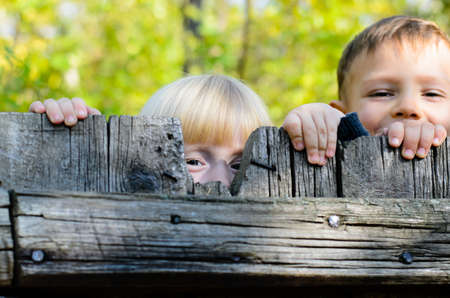 Two children, a little blond girl and boy, standing side by side peeking over an old rustic wooden fence with just their eyes visible Stockfoto