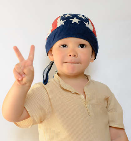 bonnet up: Close up Cute Little White Boy in Casual Polo Shirt with Bonnet Showing Peace Hand Sign on a White Background. Stock Photo