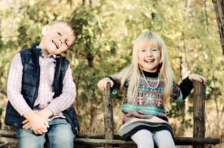 camaraderie: Close up Happy White Male and Female Kids in an Autumn Outfit Sitting on Wooden Garden Fence Stock Photo