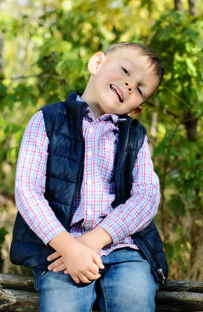 Close up Portrait of a Cute Little Boy in an Autumn Clothing Sitting on the Wooden Fence at the Garden While Smiling at the Camera photo