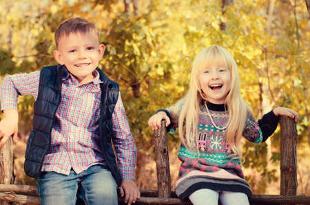 camaraderie: Happy Little Young Kids in an Autumn Style Outfits Sitting on the Wooden Garden Fence.