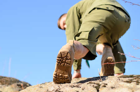 emphasizing: Young Boy Scout Climbing a Big Rock on a Hot Sunny Day, Emphasizing the Details of his Shoe Sole. Stock Photo