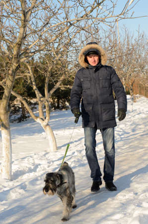 warmly: Warmly dressed man walking his dog on a lead in winter snow as they both enjoy the sunshine outdoors Stock Photo