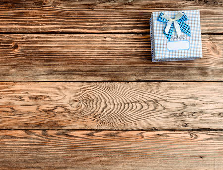 blue plaid: Square Gift Box Wrapped in Blue Plaid Paper with Blue and White Bow on Wooden Background with Copy Space seen from Above Stock Photo