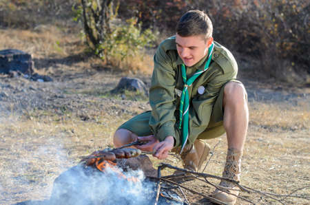 making a fire: Boy Scout in Uniform Crouching and Cooking Sausages on Sticks over Campfire