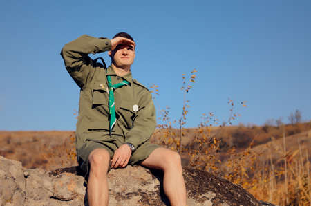 man searching: Young Boy Scout in Uniform Watching Over the Brown Field on A Sunny Day While Sitting on the Boulder.