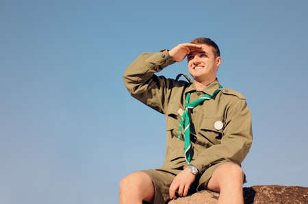 sitting man: Young Boy Scout in Uniform Watching Over the Brown Field on A Sunny Day While Sitting on the Boulder.