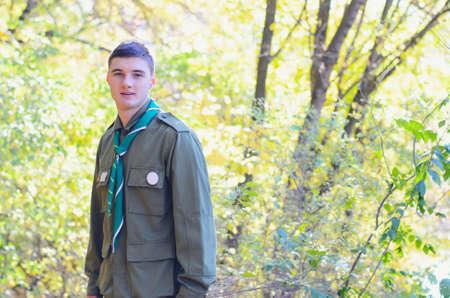 Taille-up Portret van Boy Scout dragen uniform staande in het bos op zonnige dag