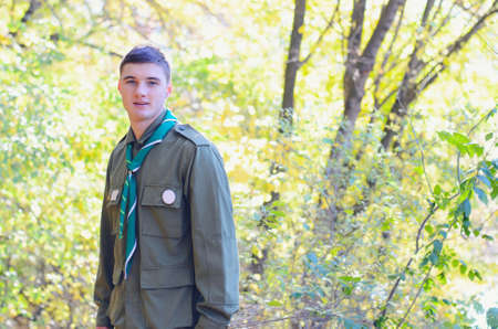 everyday scenes: Waist Up Portrait of Boy Scout Wearing Uniform Standing in Forest on Sunny Day