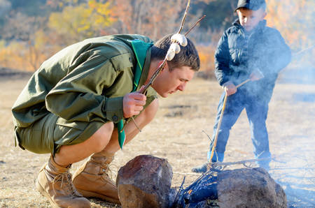 stoking: Boy Scout in Uniform Holding Sausages on Stick and Crouching Over Smoking Campfire as if Stoking or Blowing on Flame, While Young Boy Looks On