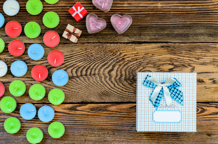 Candle with gift box and hearts on wooden background photo