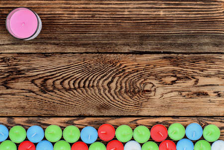 Different color candles on wooden background photo