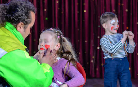 clowning: Pretty Young Girl Applied with Clown Makeup for a Stage Play by a Male Artist. Stock Photo