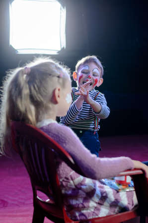 clowning: Funny Cute Boy with Mime Makeup Laughing at the Face of his Girl Play Partner While Sitting at the Backstage. Stock Photo