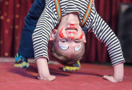 Supple agile little boy doing a back arch handstand on stage in a theatre wearing his colorful makeup as he grins at the camera from his upside down position