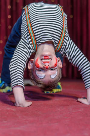 grins: Supple agile little boy doing a back arch handstand on stage in a theatre wearing his colorful makeup as he grins at the camera from his upside down position