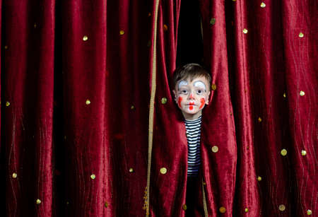 stage make up: Young Boy Wearing Clown Make Up Peering Out Through Opening in Red Stage Curtains Stock Photo