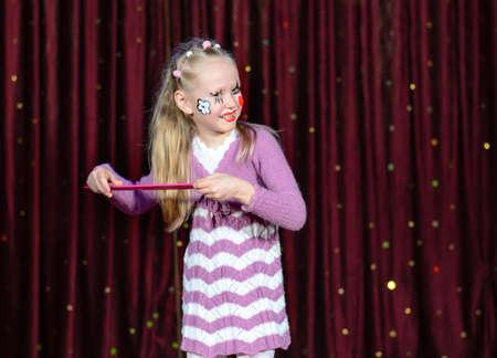 pantomima: Ni�a sonriente rubia que llevaba maquillaje pantomima se peina el pelo con una enorme peine rosa como el que se encuentra en el escenario delante de all� cortinas sonriendo a la c�mara
