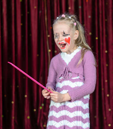stage make up: Young Blond Girl Smiling with Face Painted in Clown Make Up Holding Bright Pink Over Sized Comb on Stage with Red Curtain