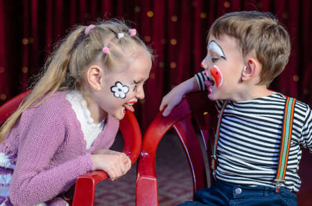 Boy and Girl Wearing Clown Make Up Sitting Side by Side and Sticking Tongues Out at Each Other photo