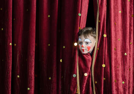 Young Boy Wearing Clown Make Up Peering Out Through Opening in Red Stage Curtains Stok Fotoğraf