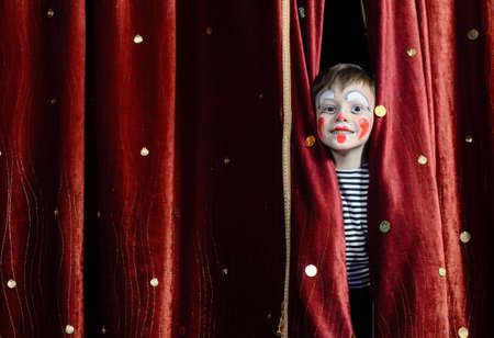Young Boy Wearing Clown Make Up Peering Out Through Opening in Red Stage Curtains 스톡 콘텐츠