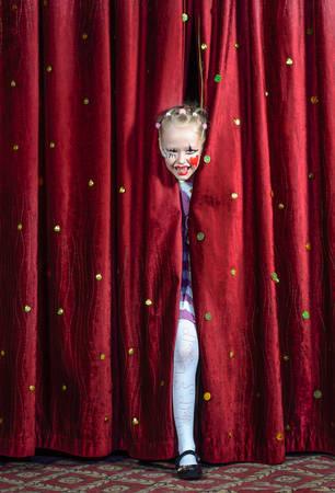 pantomima: Ni�a de realizar en una pantomima que mira a escondidas a trav�s de las cortinas en el escenario en el maquillaje con una gran sonrisa mientras espera para hacer su entrada