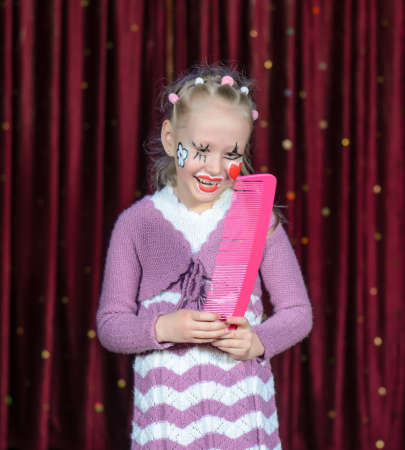 Young Blond Girl Smiling with Face Painted in Clown Make Up Holding Bright Pink Over Sized Comb on Stage with Red Curtain