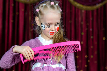 over sized: Young Blond Girl with Face Painted in Clown Make Up Brushing Hair with Over Sized Pink Comb while Standing on Stage with Red Curtain in Background