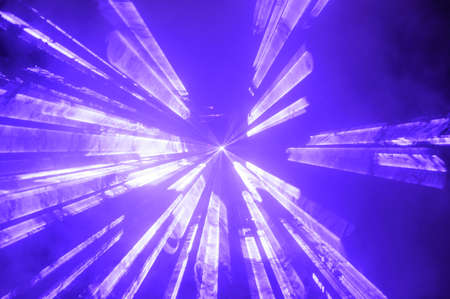 strobe: Bright blue spotlight or strobe sending vibrant colorful beams of light through the darkness at a concert or disco party
