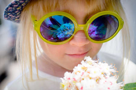 mirrored: Fashionable cute little girl wearing hat and mirrored blue round sunglasses with yellow plastic frames while smelling the white fragrant flowers of a bouquet, close-up portrait