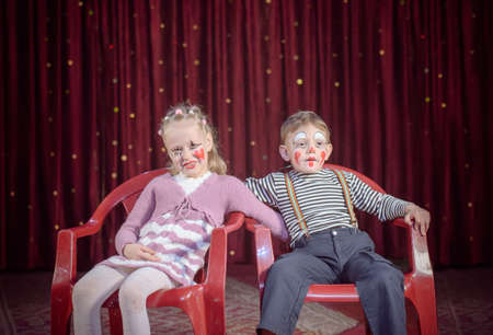 stage make up: Boy and Girl with Faces Painted in Clown Make Up Sitting in Red Chairs Side by Side on Stage with Red Curtain