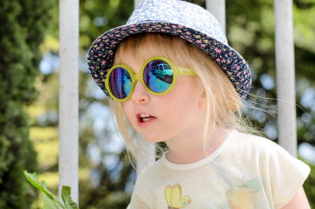mirrored: Blond little girl wearing trendy summer accessories as hat with floral pattern and mirrored sunglasses with yellow plastic frames while looking up outdoors, portrait Stock Photo
