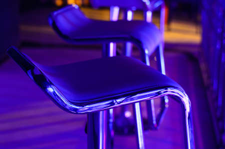 garish: Detail of Empty Bar Stool Lit in Purple Blue Light at Night Club or Bar