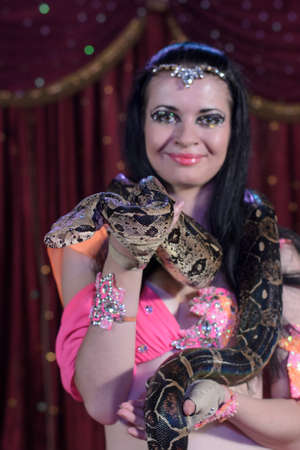 stage performer: Portrait of Female Stage Performer, Snake Charmer Holding Python Snake Wrapped Around Shoulders Standing in front of Red Stage Curtain