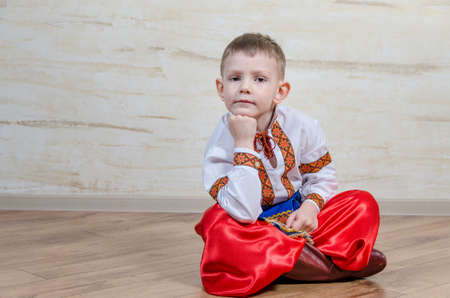 expressionless: Inquiring clever little boy with traditional folk costume sitting on the parquet floor with crossed legs while leaning his chin on hand and looking at camera with a pensive facial expression Stock Photo