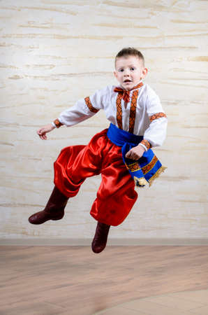 discriminating: Talented child wearing Eastern European folk costume with embroidered white shirt and belt, red pants and boots, in a mid-air leap while performing a traditional dance