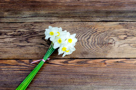 high angle: High Angle View of White and Yellow Daffodils Tied into Bouquet with Pink Ribbon on Wooden Background