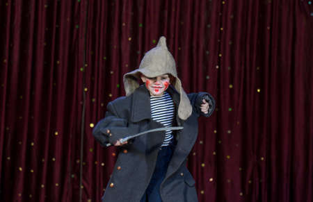 Young Boy Wearing Clown Make Up and Dressed in Over Sized Grey Coat and Floppy Hat Playing with Prop Toy Sword on Stage photo