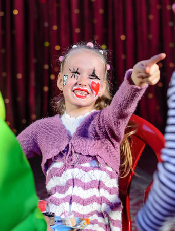 person standing: Young Blond Girl with Face Painted with Clown Make Up Smiling and Pointing Toward Other Person Standing Off Camera